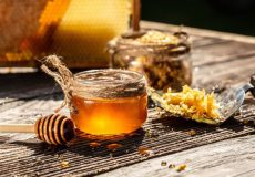 honey-bee-honeycomb-with-honey-dipper-wooden-table_114941-295
